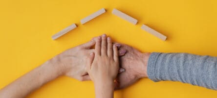 Family Stacking Their Hand On Yellow Background With Roof Made O